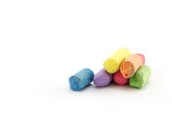 Menos giz em uma variedade de cores arranjou em um fundo branco Foto de Stock Royalty Free