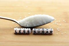 Menos texto del azúcar de bloques tejados de la letra y pila del azúcar en una cuchara que sugiere adietando concepto Imagen de archivo