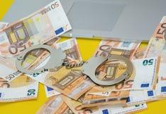 Menottes avec l'argent sur le clavier d'ordinateur portable photos stock