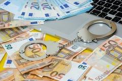 Menottes avec l'argent sur le clavier d'ordinateur portable image stock
