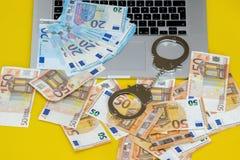 Menottes avec l'argent sur le clavier d'ordinateur portable images stock