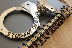 Menottes avec la dette d'étudiant de signe images libres de droits