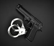 Menottes et arme à feu sur la table noire Photographie stock