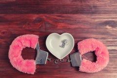 Menottes pelucheuses de rose et une soucoupe en céramique sous forme de coeur, où mensonge les clés Photos stock