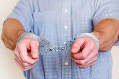 Menottes sur les poignets de l'homme détenu photographie stock