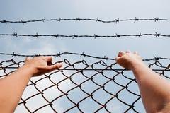 Mens achter gevangenisbars die uit bereiken Stock Afbeeldingen