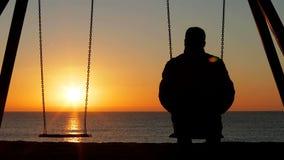 Mens alleen het overwegen zonsondergang op het strand stock video