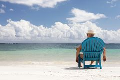 Mens als voorzitter op Caribbian-strand Stock Foto's