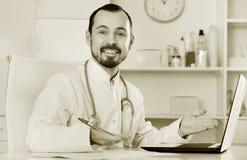 Mens arts die effectief in zijn bureau werken Royalty-vrije Stock Foto