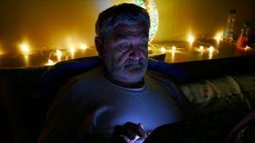 Mens in bed bij nacht met de tablet stock video