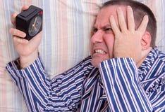 Mens in bed het letten op wekker Stock Foto