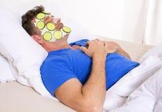 Mens in bed met gezichts stock fotografie