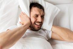 Mens in bed met hoofdkussen die aan lawaai lijden stock fotografie