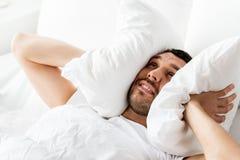 Mens in bed met hoofdkussen die aan lawaai lijden stock foto