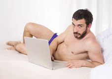 Mens in bed met laptop Royalty-vrije Stock Foto