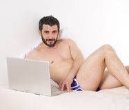 Mens in bed met laptop Stock Fotografie