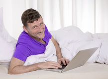 Mens in bed met laptop Royalty-vrije Stock Afbeelding