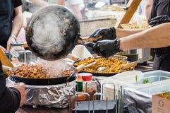 Mens behandelingspannen van oosters voedsel bij open voedselmarkt in Ljubljana, Slovenië Royalty-vrije Stock Foto's