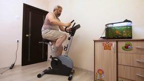 Mens belast op hometrainer met ruimte stock videobeelden