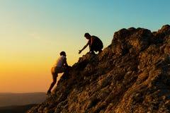 Mens Bergbeklimming met een andere Mens het Helpen Royalty-vrije Stock Fotografie