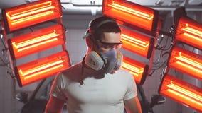 Mens beschermend masker dragen en glazen die oppoetsende machine met rode warme lichten op achtergrond houden stock videobeelden