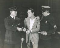 Mens in bewaring door twee politieagenten wordt genomen die Royalty-vrije Stock Foto