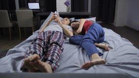 Mens bezig met smartphone, vrouwenslaap in bed stock footage