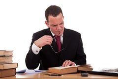 Mens bij bureau lezing en het bestuderen stock afbeelding