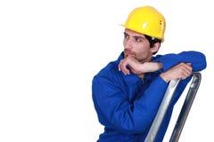 Mens bij de bovenkant van ladder wordt bevonden die stock afbeelding