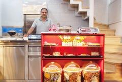 Mens bij de holding van de notenwinkel om klanten te dienen Stock Fotografie