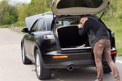 Mens bij de kant van de weg met zijn auto wordt opgesplitst die Royalty-vrije Stock Foto