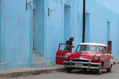 Mens bij de rode auto en de blauwe muren Royalty-vrije Stock Afbeeldingen