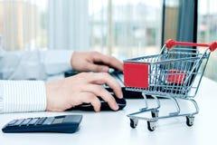 Mens bij het bureau met laptop en een miniatuurkarretje Stock Foto's
