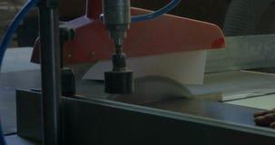 Mens bij het werk zagend hout close-up die van blad is ontsproten Een machine die hout, spaanplaat en houtvezelplaat zaagt Indust stock footage