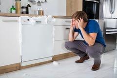 Mens bij het Zien van Schuim wordt geschokt komend uit Afwasmachine die royalty-vrije stock afbeeldingen