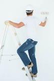 Mens bij ladder het schilderen met rol stock foto