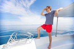 Mens bij luxe het witte boot verzenden bij open blauwe overzees royalty-vrije stock fotografie