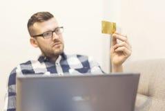 Mens bij zijn laptop holdingscreditcard Stock Afbeelding