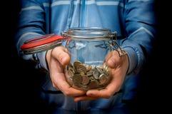 Mens in blauwe het geldkruik van de sweatshirtholding met muntstukken royalty-vrije stock afbeelding