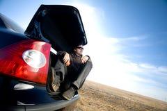 Mens in boomstam van auto stock foto's