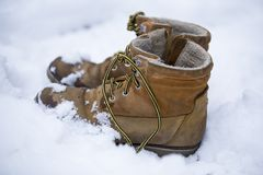 Mens brown boots in the snow, forgotten in the woods boots. Stock Photos
