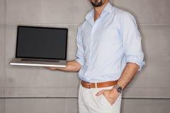 Mens in bureau dat zijn presentatie op laptop toont royalty-vrije stock afbeelding