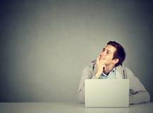 Mens in bureau, die bij bureau met laptop dagdromen, het glimlachen zitten royalty-vrije stock foto