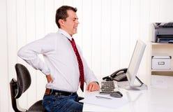 Mens in bureau met computer en rugpijn Stock Foto's