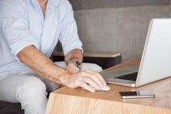 Mens in bureau met laptop stock afbeelding