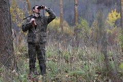 Mens in camouflage en met kanonnen in een bosriem op de lente hun Stock Foto