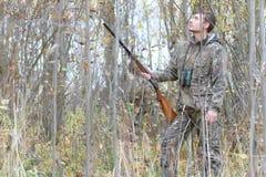 Mens in camouflage en met kanonnen in een bosriem op de lente hun Royalty-vrije Stock Afbeeldingen