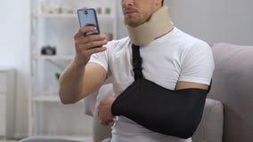 Mens in cervicale kraag en wapenslinger het babbelen smartphone thuis, rehabilitatie stock footage