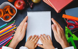Mens and childrens hands holding a notebook. School concept. Stock Photos