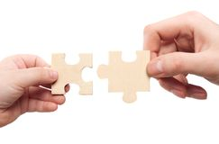 Mens and childs hands connecting puzzles Royalty Free Stock Image